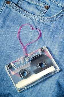 Cassette audio vintage sur un jean bleu avec du ruban rouge sorti en forme de coeur
