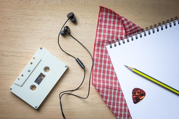 Cassette, écouteurs et cahier vierge sur bois pour fond de songwriter