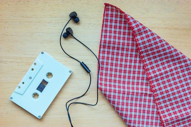 Cassette, écouteurs et cahier vierge sur bois