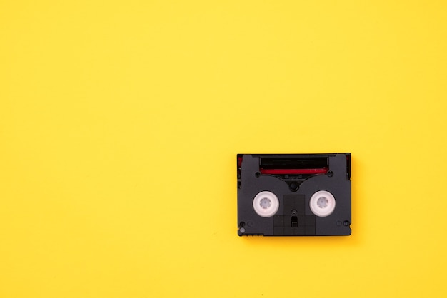 Cassette mini dv vintage utilisée pour enregistrer une vidéo en une journée. bande de film en plastique, magnétique, analogique sur fond jaune