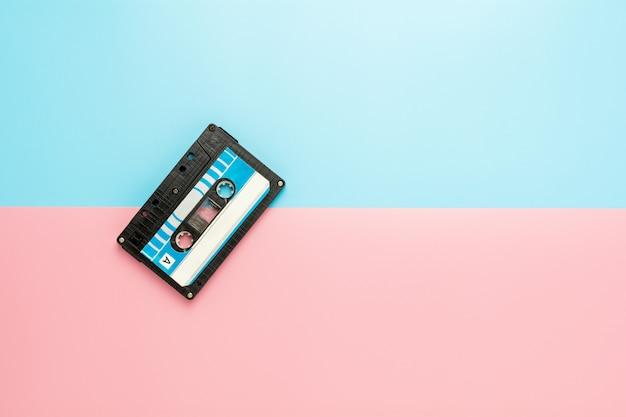 Cassette à ruban noir sur fond bleu et rose.