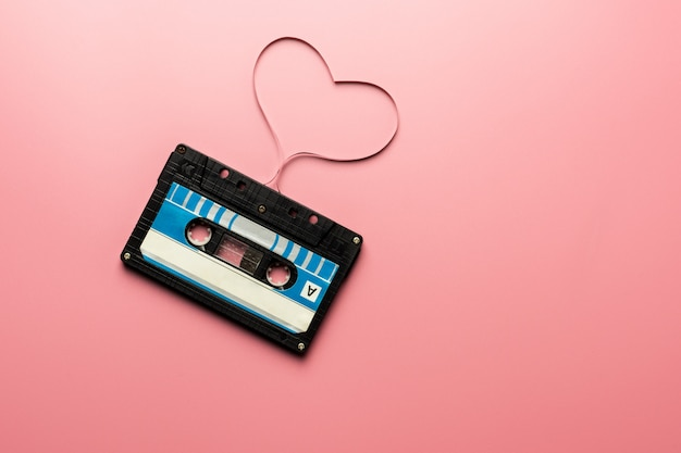 Cassette à ruban noir sur fond rose.