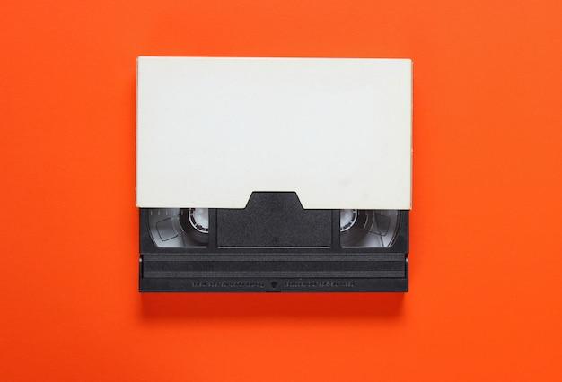 La cassette vidéo dans un étui en papier sur fond orange