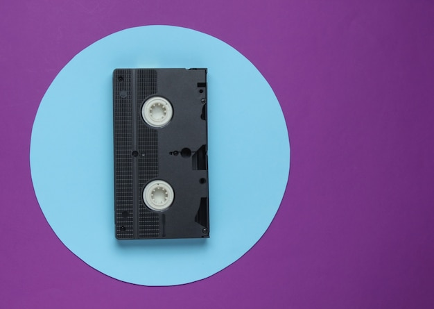 Cassette vidéo sur fond violet avec cercle pastel bleu. concept rétro minimaliste. vue de dessus