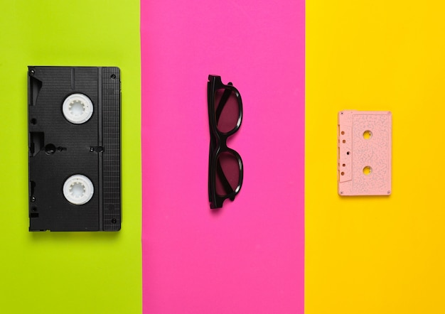 Cassette vidéo, lunettes de soleil, cassette audio sur une surface en papier multicolore. tendance minimaliste, mise à plat, vue de dessus.