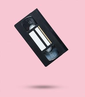 Cassette vidéo de style rétro sur rose pastel.