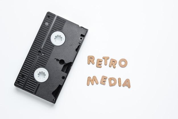 Cassette vidéo sur une surface blanche avec des mots médias rétro.