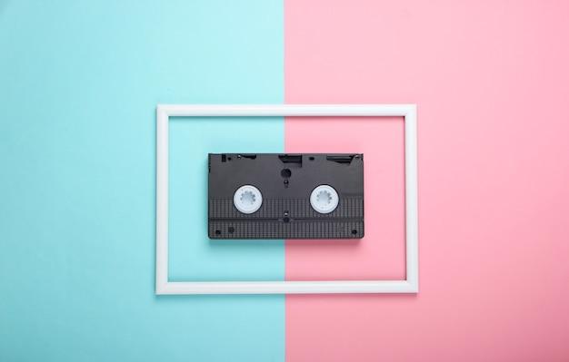 Cassette vidéo sur une surface pastel bleu rose avec cadre blanc