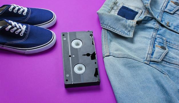 Cassette vidéo, veste en jean, baskets sur fond violet