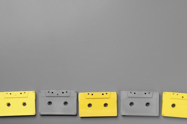Cassettes audio jaunes et grises sur fond gris vue de dessus, copiez l'espace
