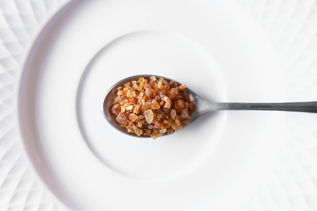 Cassonade brune dans une cuillère placée sur une plaque blanche. vue de dessus
