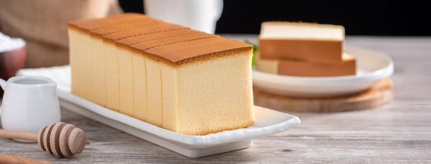 Castella (kasutera) - délicieuses tranches de gâteau éponge japonais sur une plaque blanche sur une table en bois rustique, gros plan, alimentation saine, conception de l'espace de copie.