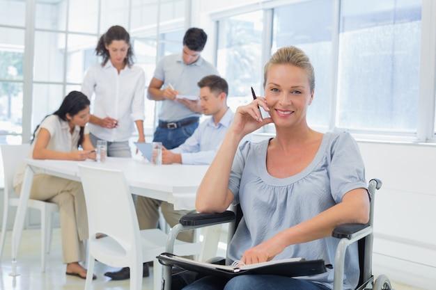 Casual femme d'affaires en fauteuil roulant, souriant à la caméra avec l'équipe derrière elle