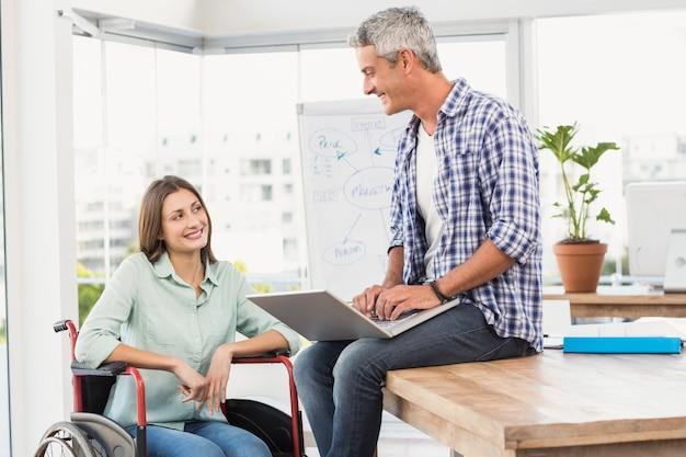 Casual femme en fauteuil roulant, parler avec un collègue