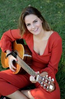 Casual fille vêtue de rouge jouant de la guitare