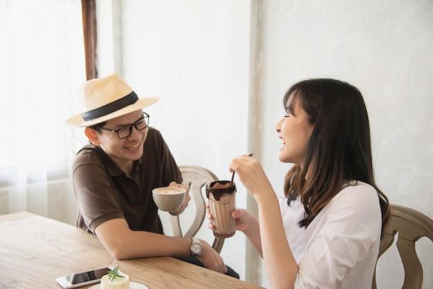Casual homme et femme parlant joyeusement tout en buvant un café
