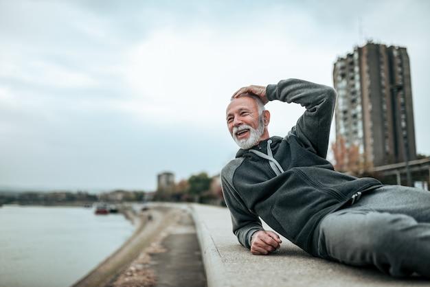 Casual homme senior relaxant au bord de la rivière dans la ville.