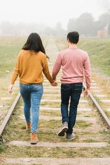 Casual jeune couple profitant d'une promenade le long des pistes
