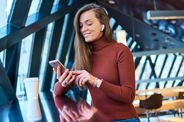 Casual jeune femme heureuse avec un casque sans fil et un téléphone mobile.
