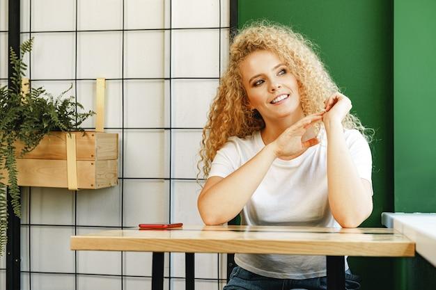 Casual jeune femme séduisante assise à la table à la cafétéria et en attente de sa commande