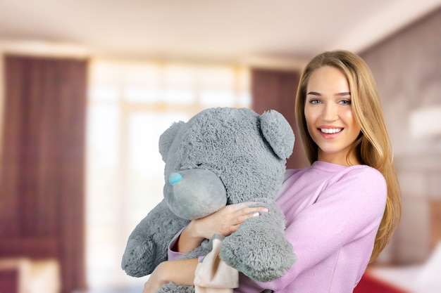 Casual jeune femme souriante tenant un ours en peluche