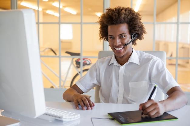 Casual jeune homme d'affaires à l'aide de numériseur et casque au bureau