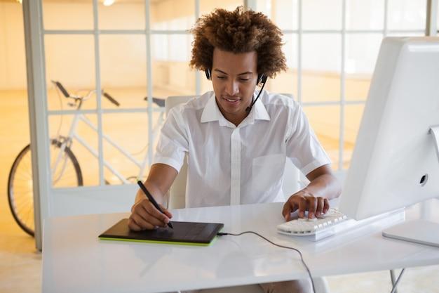 Casual jeune homme d'affaires à l'aide d'un numériseur et d'un casque au bureau