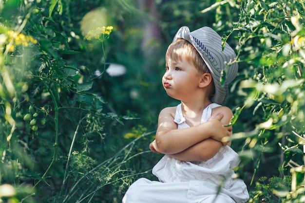 Casual se détendre sur l'herbe, garçon d'agriculteur de trois ans