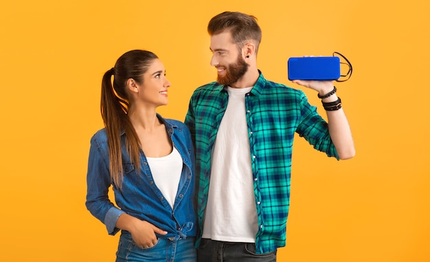 Casual young couple holding haut-parleur sans fil écouter de la musique sur orange
