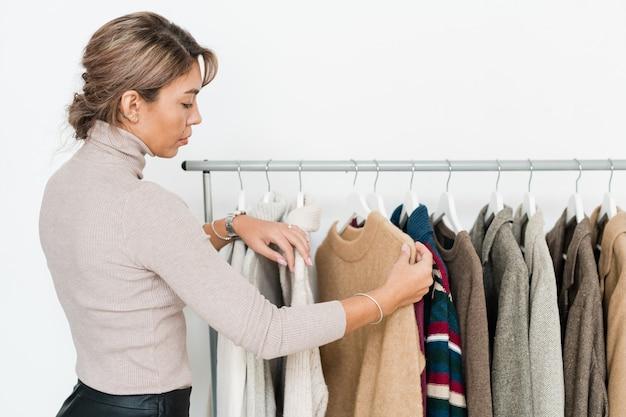 Casual young woman looking at beige pull sur rack entre autres vêtements tout en allant acheter quelque chose