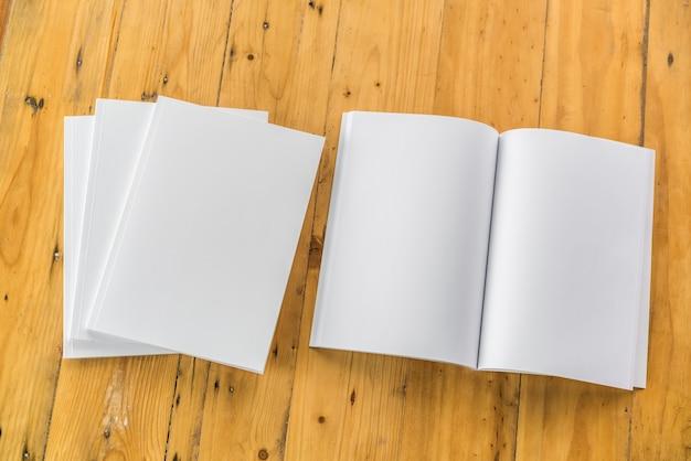 Le catalogue en blanc, les magazines, le livre se moquent sur le fond du bois.