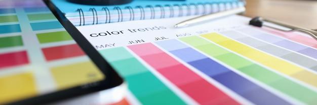 Catalogue avec échantillons de couleurs et tablette numérique allongé sur la table en gros plan