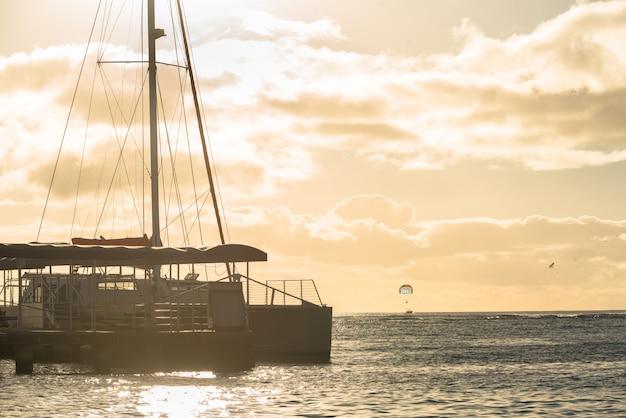 Catamaran amarré sur la plage de waikiki au coucher du soleil à honolulu, hawaii