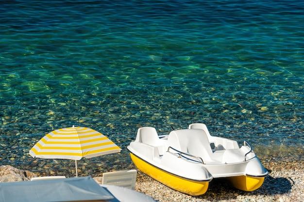 Catamaran sur la plage de galets avec parasol et mer cristalline