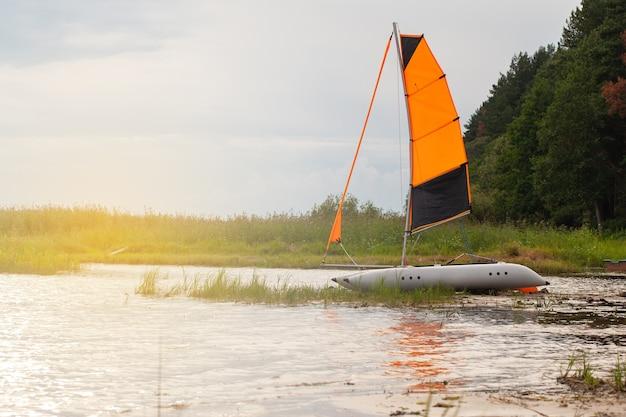 Catamaran à voile gonflable avec voiles surélevées sur la rivière près du rivage. vue latérale, soleil flare. horizontal.