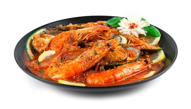 La cataplana de fruits de mer est un plat spécial (wok) pour préparer des fruits de mer au portugal. plat de cuisine le style se vante d'une grande variété de décorations avec du basilic doux et une vue latérale en forme de fleur de poireau sculpté