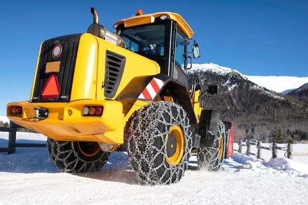 Caterpillar avec de grandes chaînes sur la neige