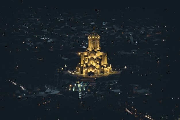 La cathédrale géorgienne tsminda sameba illuminée la nuit à tbilissi, géorgie