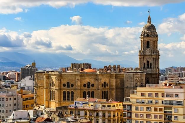 Cathédrale de la ville de malaga par une journée ensoleillée avec des nuages dans les montagnes.