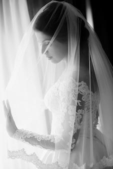 Caucasian belle femme mariée en robe blanche européenne traditionnelle debout près de la fenêtre