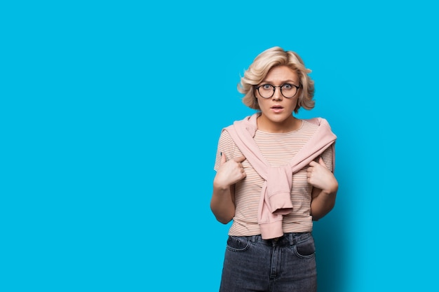 Caucasian blonde woman pointant vers elle tout en regardant choqué à travers des lunettes sur un fond bleu avec un espace libre