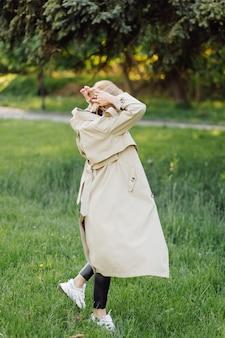 Caucasian blonde woman wearind trench sourire joyeusement le jour de printemps ensoleillé à l'extérieur à pied dans le parc