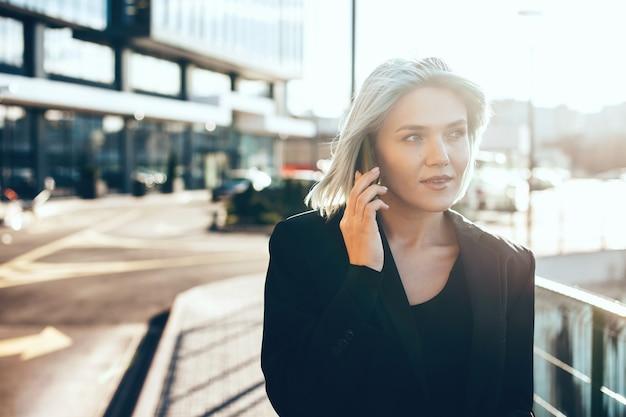 Caucasian businesswoman ayant une discussion téléphonique tout en posant à l'extérieur devant le soleil