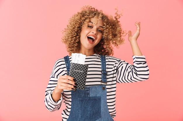 Caucasian curly woman 20s tenant un passeport et des billets de voyage en position debout