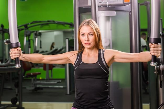 Caucasian fitness woman travaille sur machine à papillons dans la salle de sport