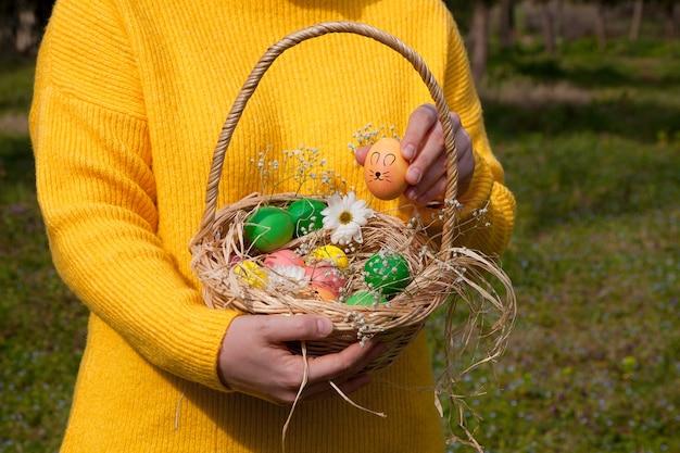 Caucasian girl holding oeufs de pâques dans le panier avec des fleurs et des bonbons