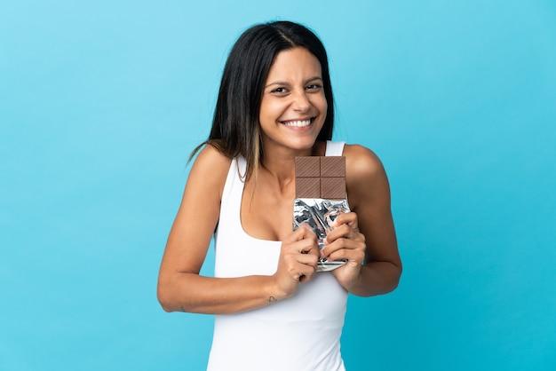 Caucasian girl isolé sur fond bleu en prenant une tablette de chocolat et heureux
