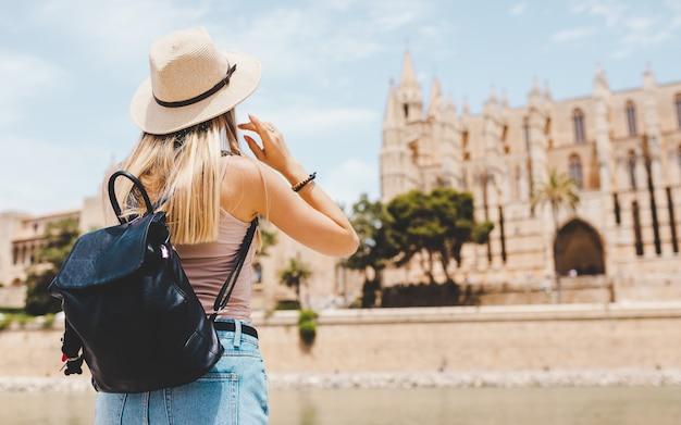 Caucasian girl touriste au chapeau à la découverte de la nouvelle ville en été