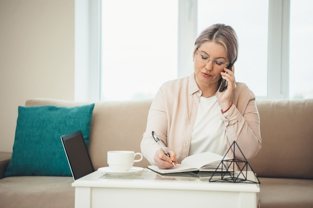 Caucasian senior woman talking on phone tout en écrivant et travaillant à distance à l'ordinateur à la maison