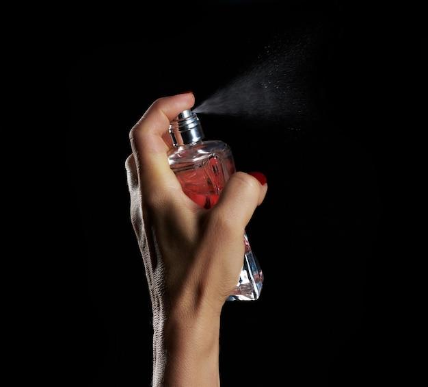 Caucasian woman détient une bouteille en verre transparent avec parfum dans sa main et appuie sur le spray, gros plan, fond noir